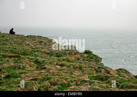 A man fishes on rocks at Sagres Cape cliffs, Portugal - Stock Photo