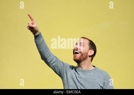 Portrait of young man pointing on something in front of yellow background - Stock Photo