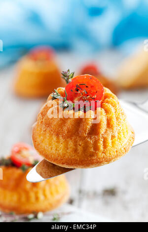 Mini Gugelhupf filled with cream cheese garnished with tomato and marjoram - Stock Photo