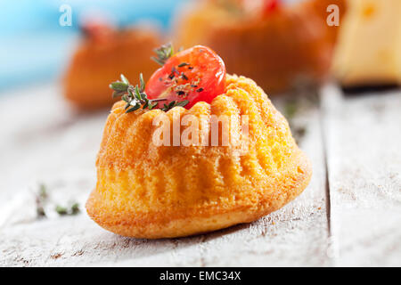Mini Gugelhupf filled with cream cheese and ricotta garnished with tomato and marjoram - Stock Photo
