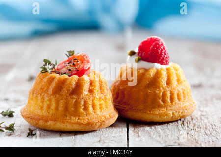 Two mini Gugelhupf filled with cream cheese and ricotta garnished with tomato and raspberry - Stock Photo