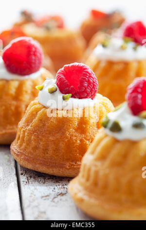 Mini Gugelhupf filled with cream cheese and ricotta garnished with raspberry and pistachio - Stock Photo