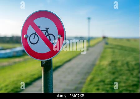 Germany, Neuharlingersiel, no bicycles sign on dike - Stock Photo