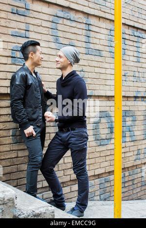 China, Hong Kong, gay couple at house wall - Stock Photo
