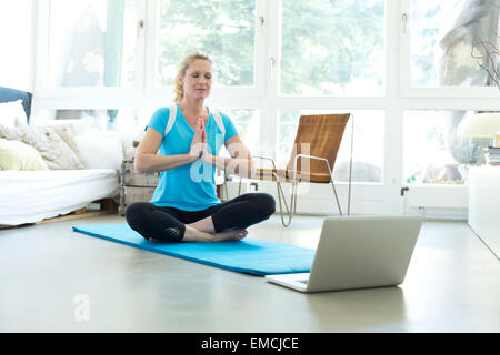 Woman with laptop practicing yoga on gym mat in living room - Stock Photo