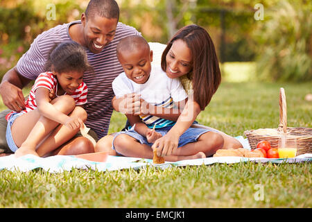 Family Having Picnic In Garden Together - Stock Photo