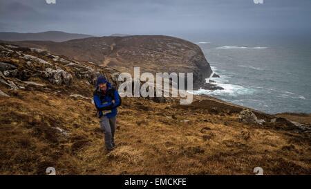 Walker ascending coastal walk from Isle of Barra sea stacks, Outer Hebrides, Scotland, UK - Stock Photo