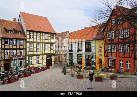 Quedlinburg, Germany - April 16, 2015: Tourist taking photograph of the colorful half-timbered houses on Schlossberg. - Stock Photo