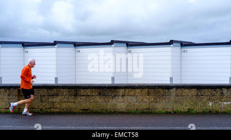 A male jogger runs past a row of beach huts on worthing promande - Stock Photo