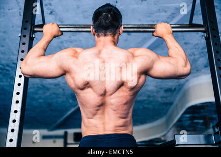 Back view portrait of a muscular man pulling up at gym - Stock Photo