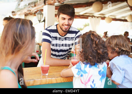 Man Making Children Fruit Smoothies In Restaurant - Stock Photo