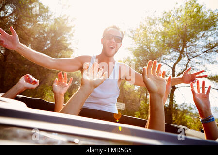 Group Of Young Friends Dancing In Back Of Open Top Car - Stock Photo
