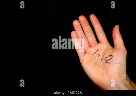 1+1=2 written on a white man's hand photographed against a black background. - Stock Photo