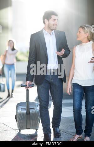 Businessman pulling suitcase walking next to woman - Stock Photo