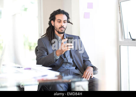 Businessman with dreadlocks sitting in an office looking at smartphone - Stock Photo