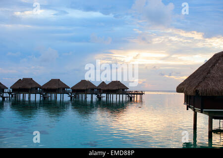 Over water villas at sunset - Stock Photo