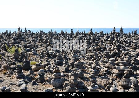 Memorial statues of stones made by travelers and visitors on the beach in Puerto de la Cruz, Tenerife. - Stock Photo