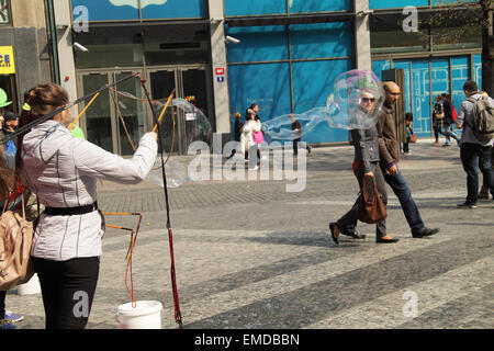 young girl making big soap bubbles in the center of Prague, a couple passing by, being caught in one of the bubbles. - Stock Photo