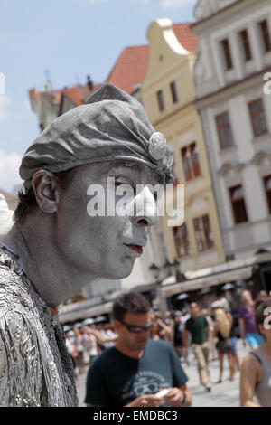 Male Street performer dressed and painted in silver, performs on Stare Mesto Square in Prague, with tourists in - Stock Photo