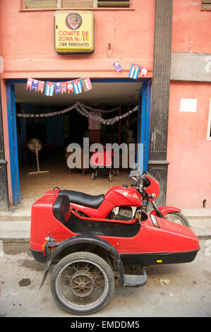 HAVANA, CUBA - JUNE 2011: Red motorcycle sidecar parked outside a Communist Party office in central Havana. - Stock Photo