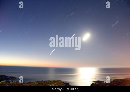 Stars and moon long exposure over ocean - Stock Photo