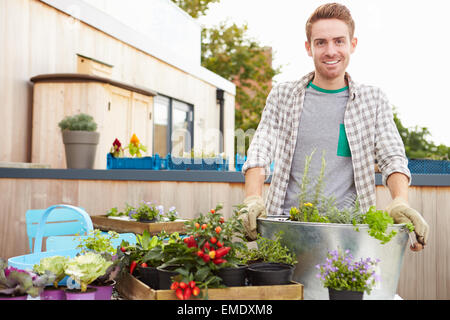 Man Planting Container On Rooftop Garden - Stock Photo