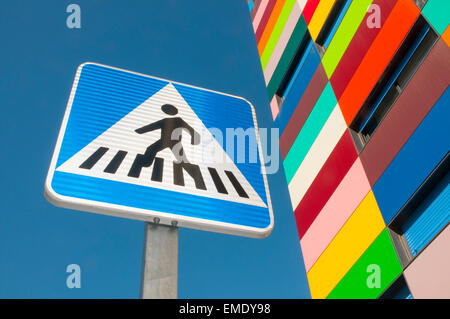 Pedestrian crossing sign and Colorines building, view from below. PAU Carabanchel, Madrid, Spain. - Stock Photo