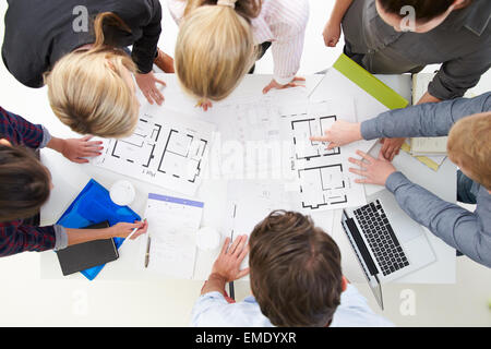 Overhead View Of Architects Discussing Plans In Office - Stock Photo