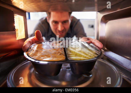 Man Putting TV Dinner Into Microwave Oven To Cook - Stock Photo