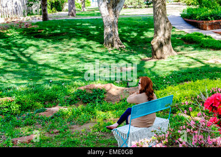 A Caucasian, red-haired woman sits on a bench and enjoys a Spring day in Will Rogers park in Oklahoma City, Oklahoma,USA. - Stock Photo