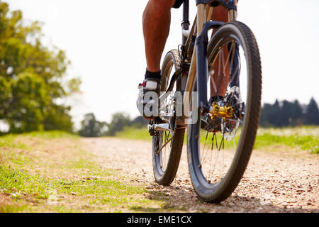 Close Up Of Man Riding Mountain Bike On Countryside Path - Stock Photo