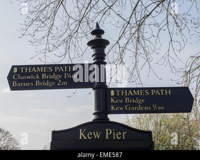 Sign for Kew Pier,Kew Gardens,River Thames tow path showing distances to Chiswick Bridge,Barnes Bridge,Kew Bridge,Kew - Stock Photo