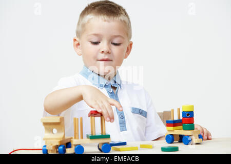 Pre-School Pupil Playing With Wooden Toy Train - Stock Photo