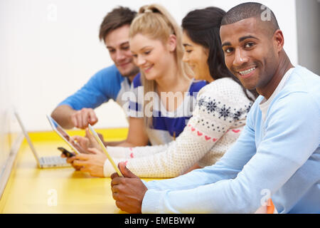 Group Of College Students Using Digital Devices - Stock Photo
