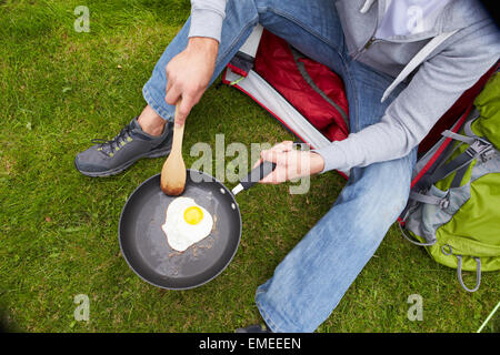 Man On Camping Holiday Frying Egg In Pan - Stock Photo