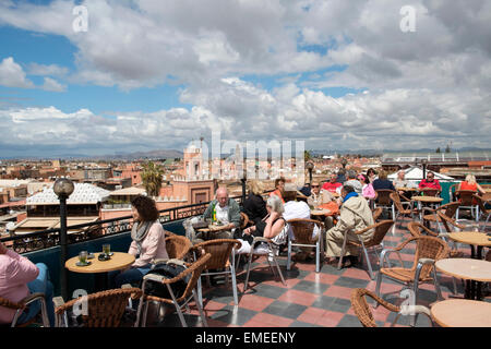 Tourists sit on rooftop terrace at Cafe du France on Jamaa el Fna square and marketplace in Marrakech, Morocco. - Stock Photo