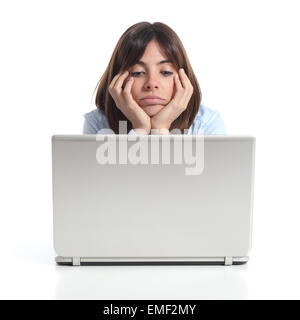 Bored woman watching a laptop isolated on a white background - Stock Photo