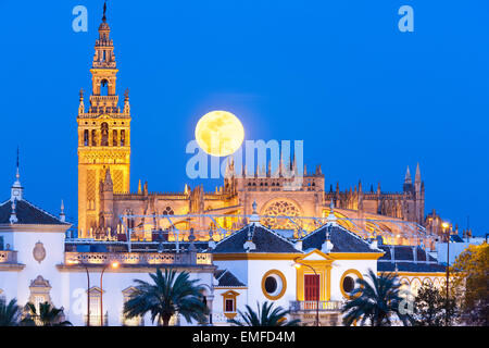 Seville Spain Seville Skyline with full moon rising behind La Giralda tower, Seville Cathedral de Sevilla, and Plaza - Stock Photo