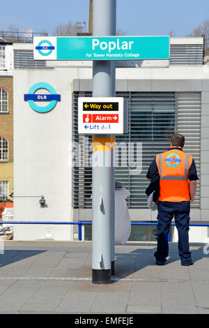 Docklands Light Railway employee standing on Poplar station platform with DLR depot and logo beyond - Stock Photo