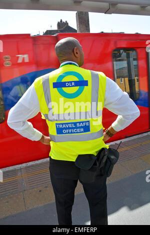 Docklands Light Railway 'Travel Safe Officer' standing on station platform as train arrives - Stock Photo