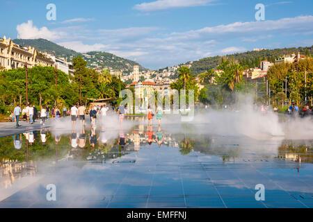 NICE, FRANCE - OCTOBER 2, 2014: People walking through soaking fountain on Promenade du Paillon reflecting the city - Stock Photo