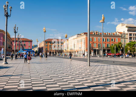 NICE, FRANCE - OCTOBER 2, 2014: People walking on Place Massena, main pedestrian square of the city. Modern statues - Stock Photo