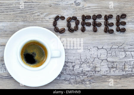 Filled espresso cup with text coffee out of beans from above - Stock Photo