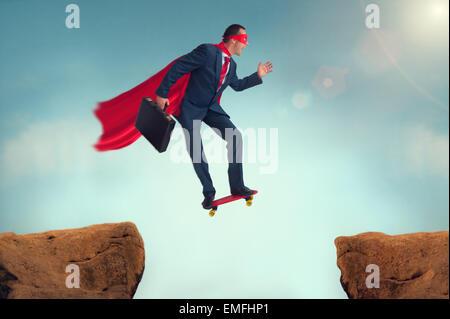 superhero businessman challenge making a risky leap of faith on a skateboard - Stock Photo