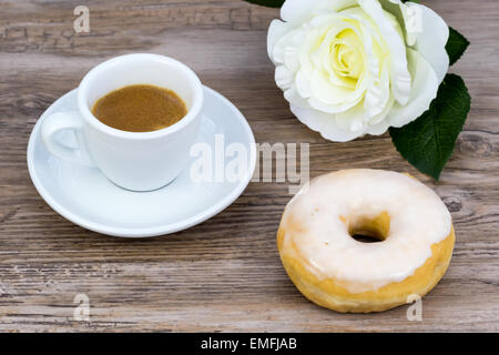 Espresso with a glazed donut and a white rose in blurred background on a wooden table from above - Stock Photo