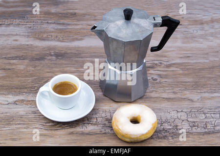 Espresso with espresso maker and a glazed donut on a wooden table from slightly above - Stock Photo