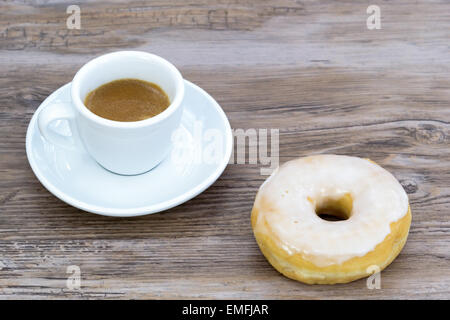 Espresso with a glazed donut on a wooden table slightly blurred background from above - Stock Photo