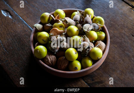 cob nuts and crab apples in wooden bowl on table - Stock Photo