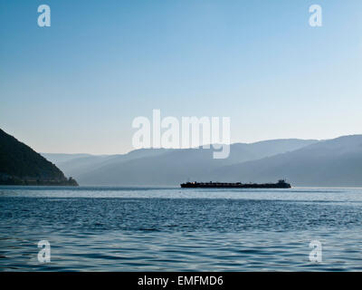 A barge passing the Iron Gate  on the Danube in Serbia - Stock Photo