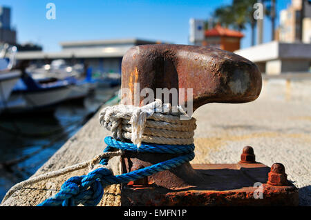 closeup of some ropes tied on a rusty mooring in a port - Stock Photo